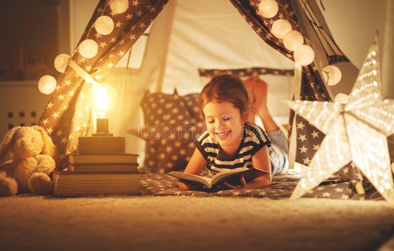 Gelukkig kindmeisje die en boek in dark in tent lezen bij ho lachen royalty-vrije stock foto's