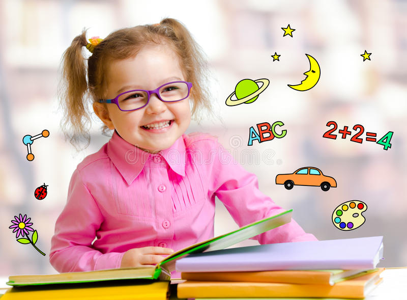 Gelukkig kindmeisje die in glazen boeken in bibliotheek lezen stock foto's