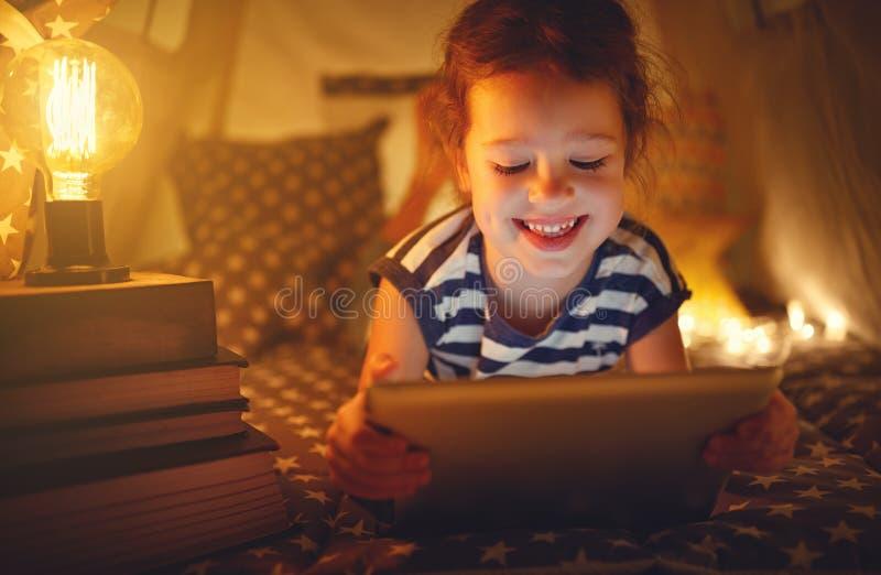 Gelukkig kindmeisje die met tabletpc in dark in tent thuis lachen stock foto