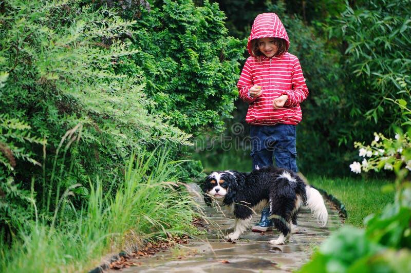 Gelukkig kindmeisje die onder de regen in de zomertuin lopen met haar hond stock afbeelding