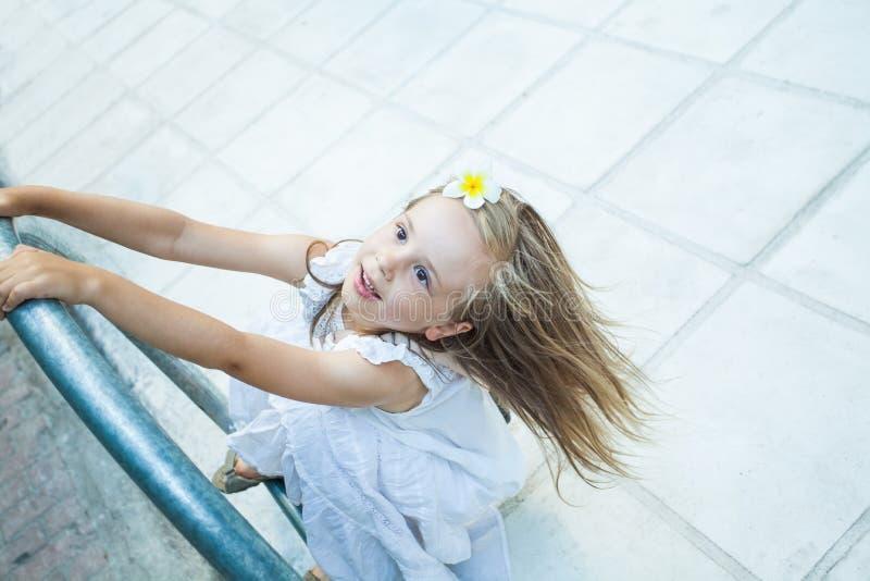 Gelukkig Kindmeisje in het witte kleding spelen dichtbij met weg stock fotografie