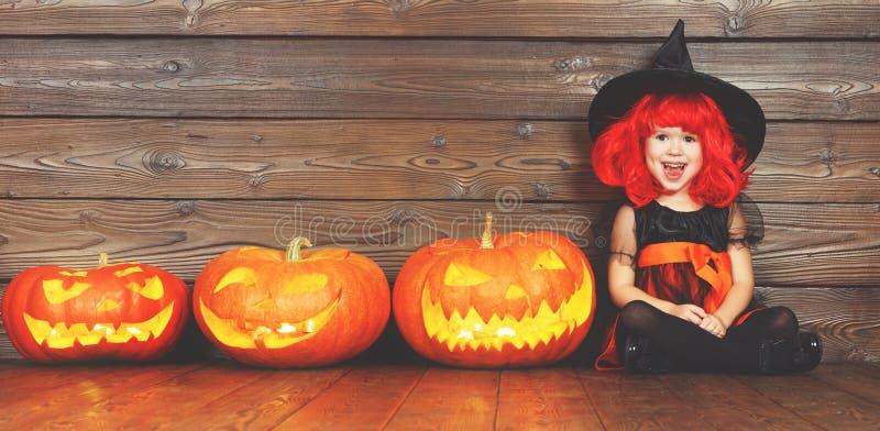 Gelukkig kindmeisje in kostuumheks voor Halloween met pompoenen stock fotografie