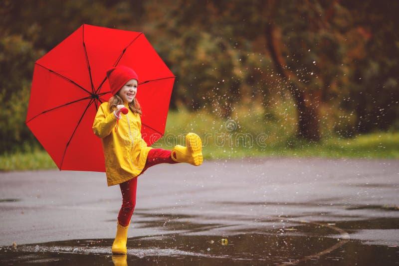 Gelukkig kindmeisje met een paraplu en rubberlaarzensprong in puddl stock afbeelding