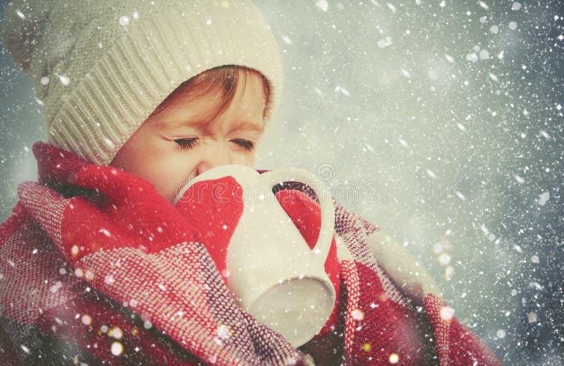 Gelukkig kindmeisje met kop van hete drank op de koude winter in openlucht stock afbeeldingen