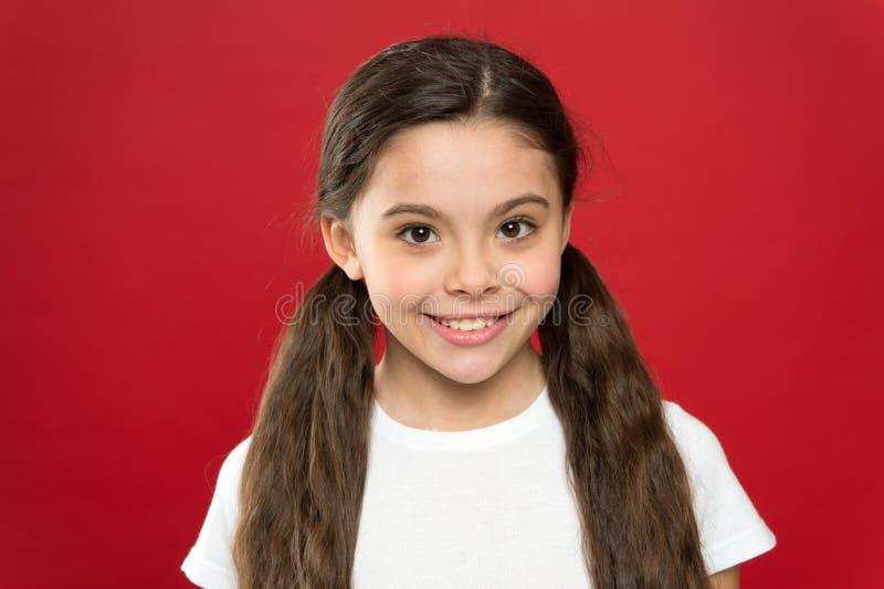 Gelukkig kindmeisje met lang haar op rode achtergrond Geluk en vreugde Positieve emoties Kinderverzorging en opvoeding kid stock fotografie