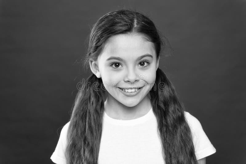 Gelukkig kindmeisje met lang haar op rode achtergrond Geluk en vreugde Positieve emoties Kinderverzorging en opvoeding kid stock afbeelding