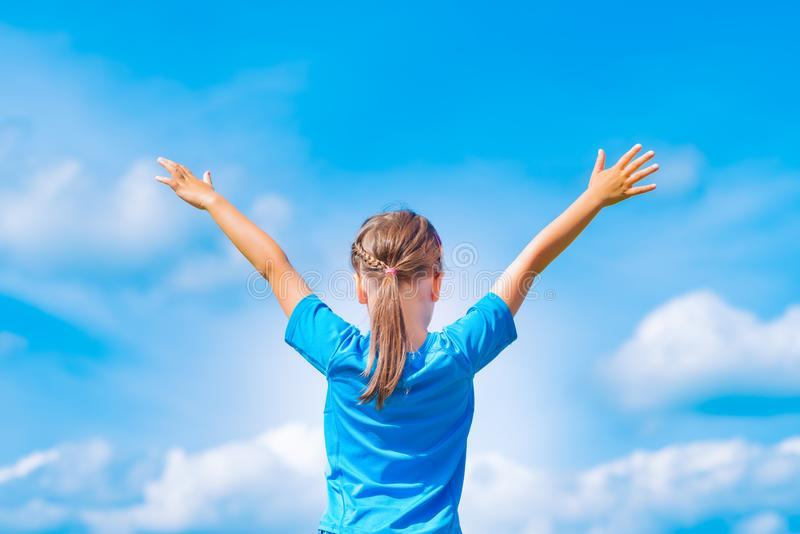 Gelukkig kindmeisje met open wapens openlucht onder blauwe hemel Jonge gi royalty-vrije stock afbeelding