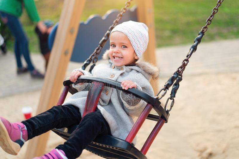 Gelukkig kindmeisje op schommeling in zonsondergangdaling Weinig jong geitje het spelen in de herfst op het aardpark stock foto's
