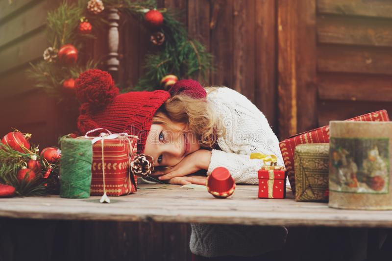 Gelukkig kindmeisje in rode hoed en sjaal verpakkende Kerstmisgiften bij comfortabel buitenhuis, dat voor Nieuwjaar en Kerstmis w stock afbeeldingen