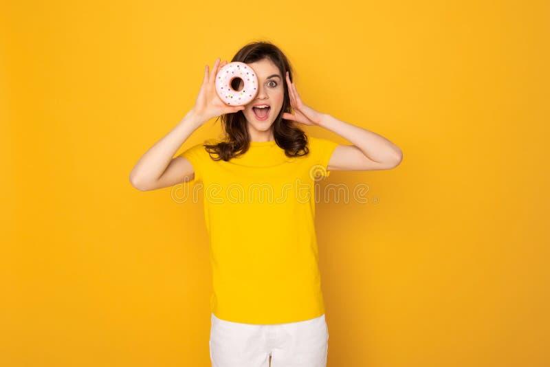 Gelukkig lachend meisje die van gat van doughnut kijken royalty-vrije stock foto