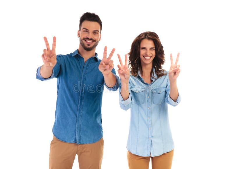 Gelukkig lachend toevallig paar die het overwinningsteken maken royalty-vrije stock foto