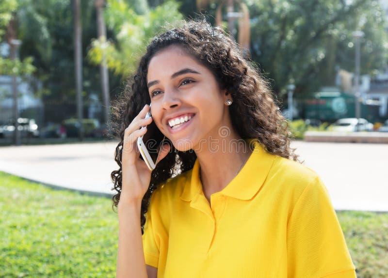 Gelukkig Latijns-Amerikaans meisje die met lang donker haar bij telefoon spreken stock afbeelding