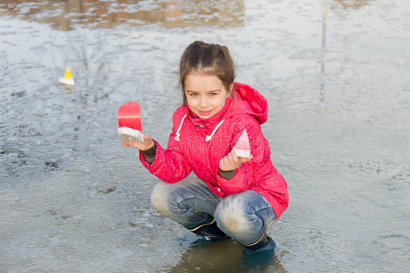 Gelukkig leuk meisje die in regenlaarzen met met de hand gemaakte kleurrijke schepen in de de lentekreek spelen die zich in water stock afbeeldingen