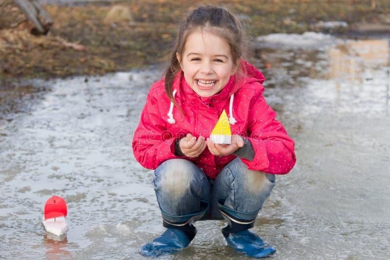 Gelukkig leuk meisje die in regenlaarzen met schepen in de de lentekreek spelen die zich in water bevinden stock foto