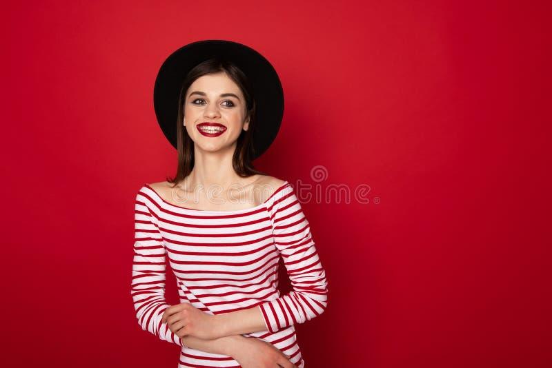 Gelukkig leuk meisje in gestreepte blouse en zwarte hoed stock foto's