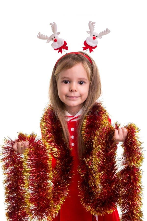 Gelukkig leuk meisje met hertenhoornen en klatergoud rond de hals en de handen Concept: Kerstmis of Gelukkige Nieuwjaarvakantie stock foto