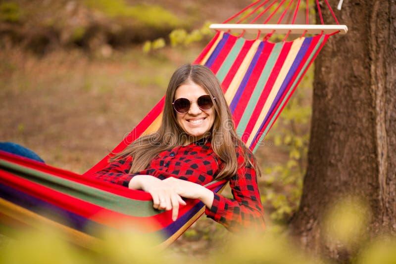 Gelukkig Levensstijlconcept Mooie onbezorgde vrouw in zonnebril in bos die gelukkig in openlucht terwijl rust op hangmat zijn stock foto's