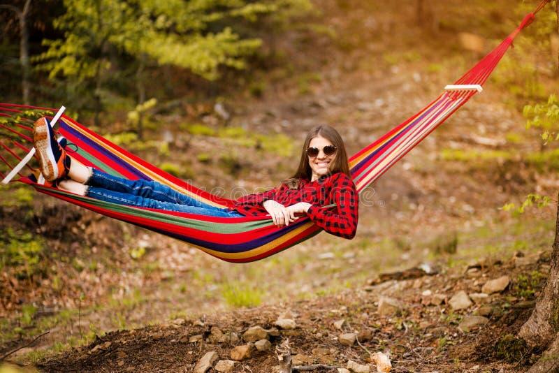 Gelukkig Levensstijlconcept Mooie onbezorgde vrouw in zonnebril in bos die gelukkig in openlucht terwijl rust op hangmat zijn stock fotografie