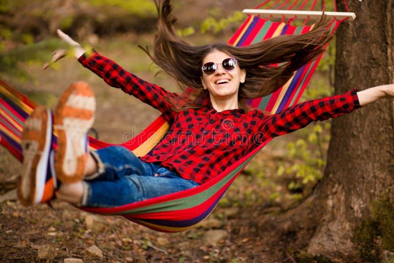 Gelukkig Levensstijlconcept Mooie onbezorgde vrouw in zonnebril in bos die gelukkig in openlucht terwijl rust op hangmat zijn royalty-vrije stock foto's