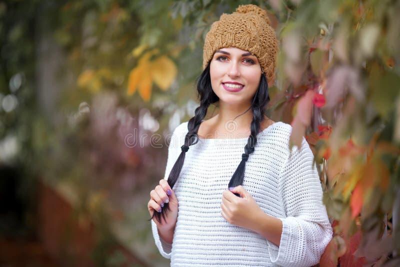Gelukkig levensstijlportret van een mooi jong modelmeisje met een glimlach in een warme de herfsthoed royalty-vrije stock afbeeldingen