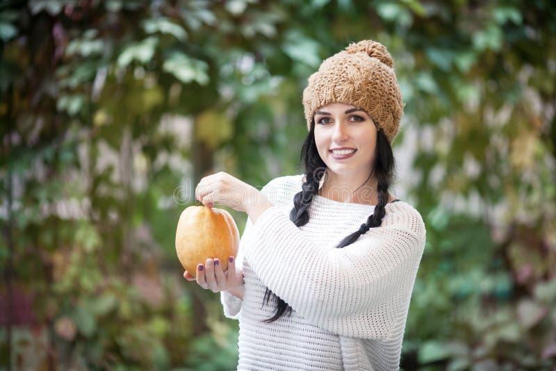 Gelukkig levensstijlportret van een mooie jonge modelvrouw met een pompoen in haar handen royalty-vrije stock foto
