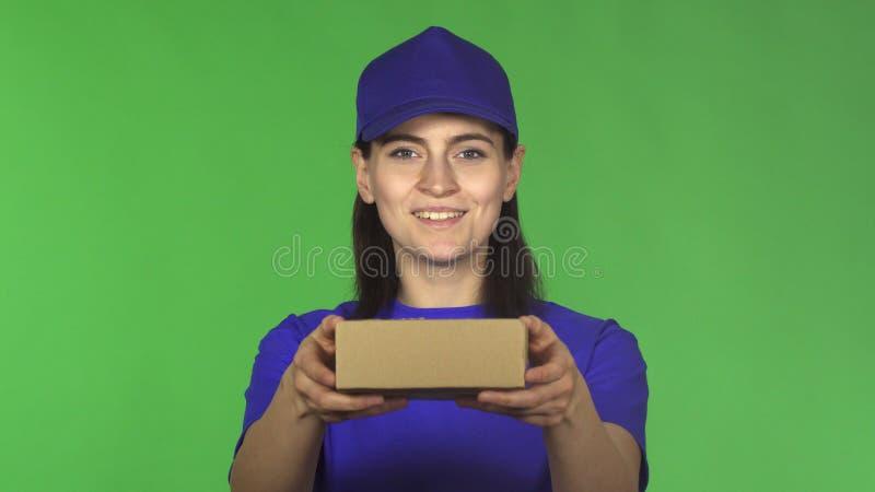 Gelukkig leveringsvrouw het glimlachen het standhouden klein pakket aan de camera royalty-vrije stock afbeelding