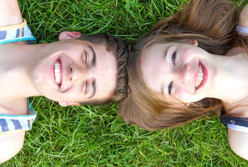 Gelukkig liefdepaar die in het gras liggen royalty-vrije stock afbeelding