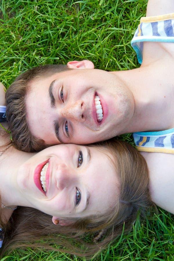 Gelukkig liefdepaar die in het gras liggen stock afbeelding