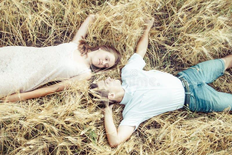 Gelukkig in liefdepaar het ontspannen op gebied stock afbeelding