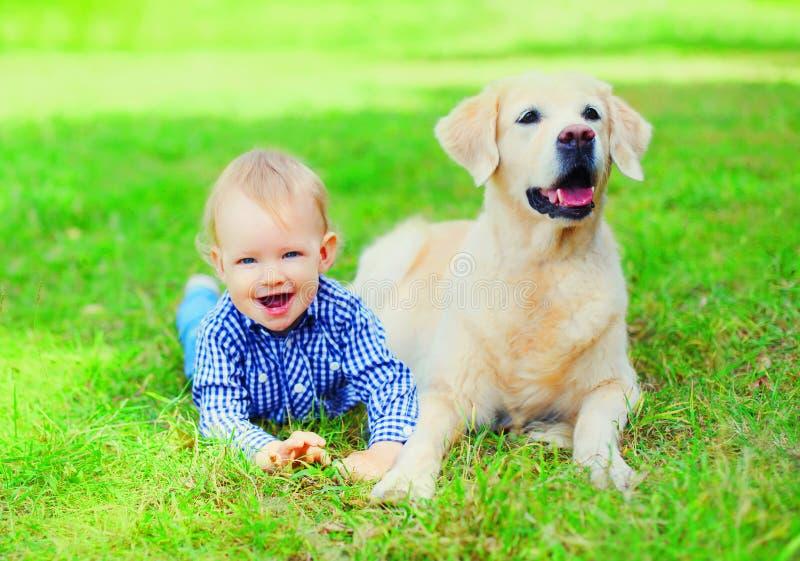 Gelukkig liggen weinig jongenskind en Golden retrieverhond samen op het gras op de zomerpark stock afbeelding