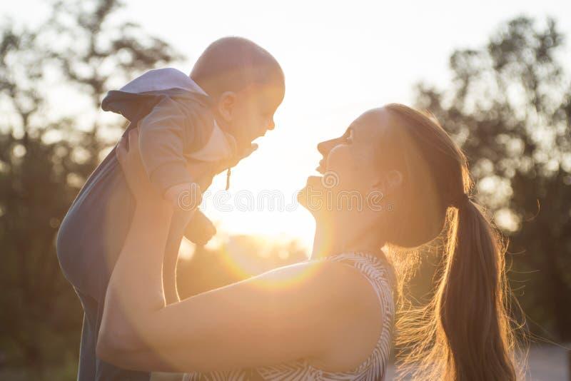 Gelukkig mamma die haar leuke baby op zonsondergangachtergrond houden Backlightsilhouet van een moeder die haar jong geitje fokke stock foto's
