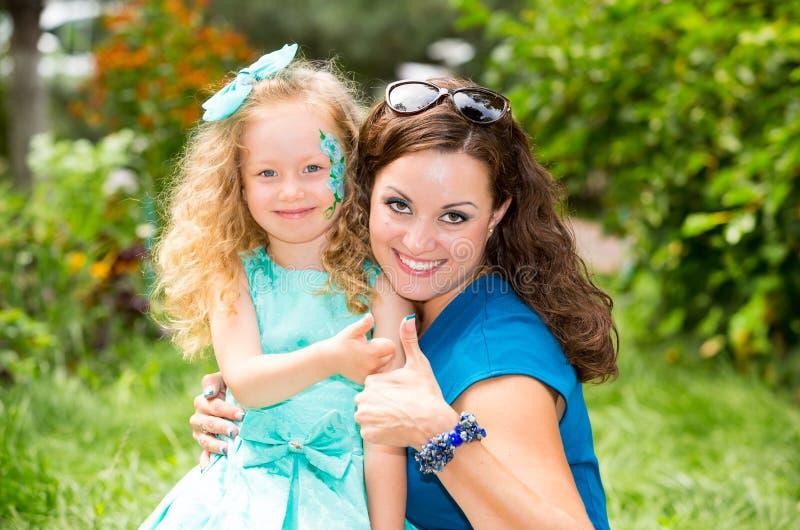 Gelukkig mamma en kindmeisje die in openlucht koesteren Het concept kinderjaren en familie De moeder en het jonge geitje van de p stock fotografie