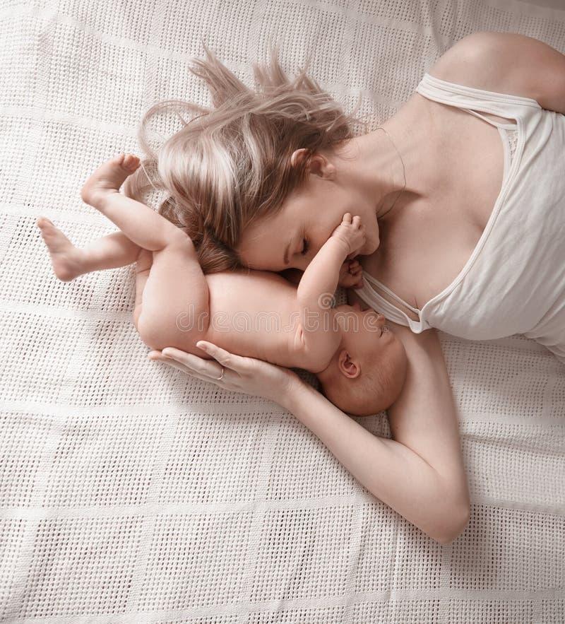 Gelukkig mamma met het pasgeboren baby liggen op het bed stock fotografie