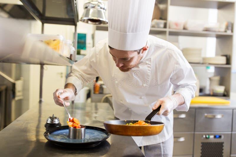 Gelukkig mannelijk chef-kok kokend voedsel bij restaurantkeuken stock afbeelding