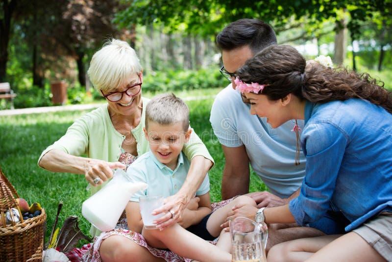 Gelukkig mannetje en wijfje die en van picknick met buiten kinderen spelen genieten royalty-vrije stock afbeelding