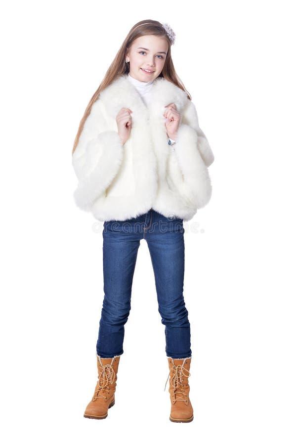 Gelukkig meisje in bontjas stellen ge?soleerd op witte achtergrond stock afbeelding