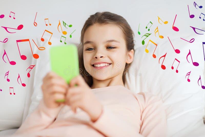 Gelukkig meisje dat in bed met smartphone over nota's ligt stock foto's