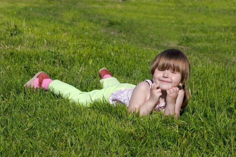 Gelukkig meisje dat op gras rust stock foto's