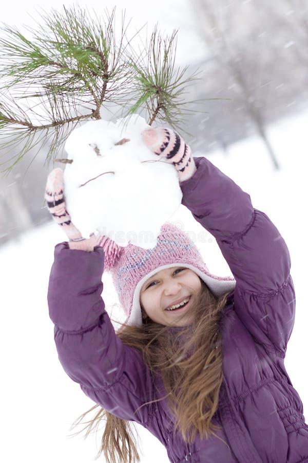 Gelukkig meisje dat sneeuwman maakt stock foto
