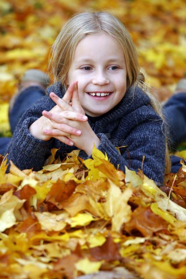 Gelukkig meisje in de bladeren van de Herfst stock afbeeldingen