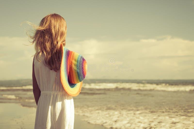 Gelukkig meisje in de hoed die zich op het strand bij de dag t bevinden stock afbeeldingen
