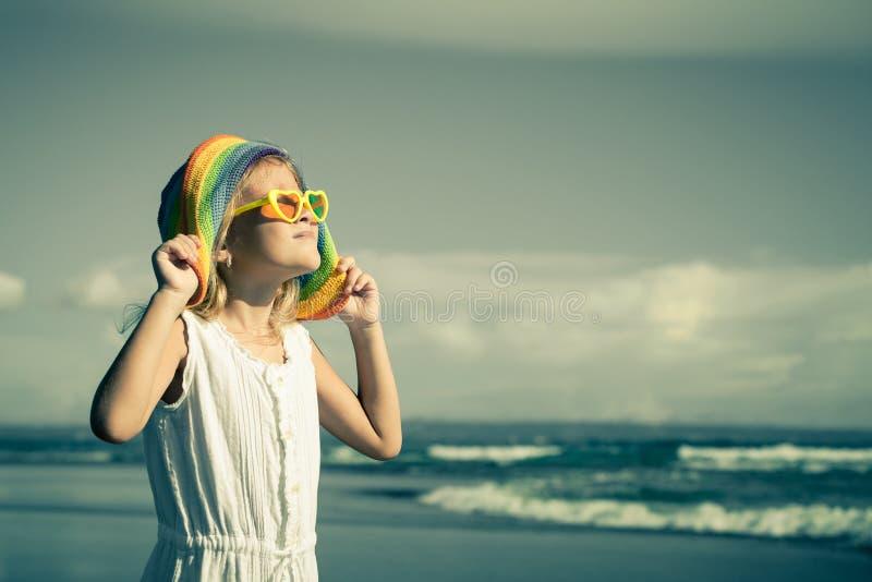 Gelukkig meisje in de hoed die zich op het strand bij de dag t bevinden royalty-vrije stock foto