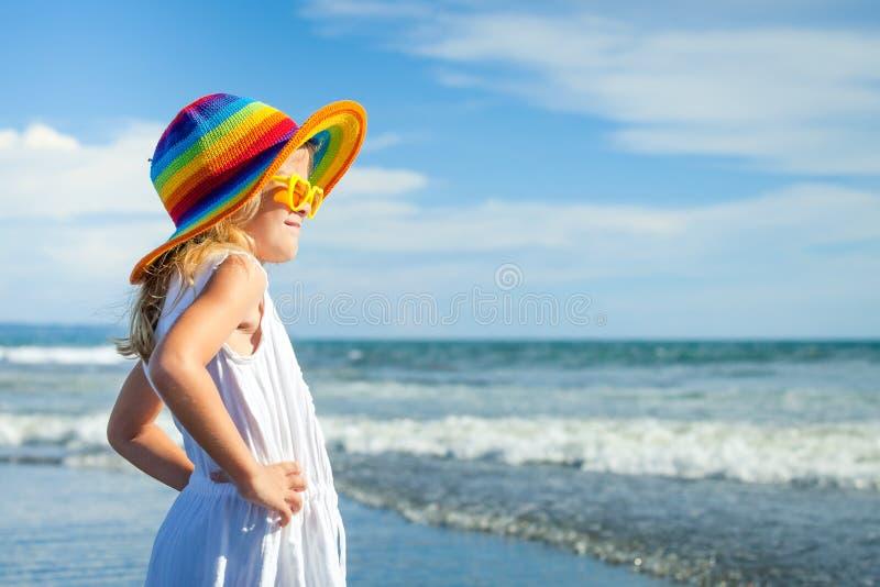Gelukkig meisje in de hoed die zich op het strand in de dag t bevinden royalty-vrije stock foto