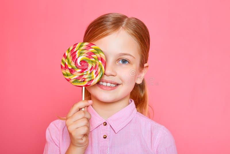 Gelukkig meisje die één oogsuikergoed op roze achtergrond behandelen stock fotografie