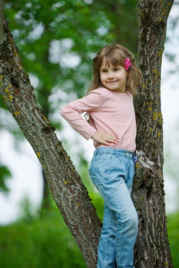 Gelukkig meisje die aan de boom beklimmen stock foto