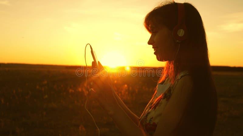 Gelukkig meisje die aan muziek luisteren en in de stralen van een mooie zonsondergang dansen jong meisje in hoofdtelefoons en met royalty-vrije stock afbeelding