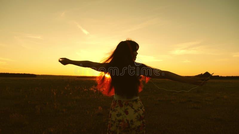 Gelukkig meisje die aan muziek luisteren en in de stralen van een mooie zonsondergang in het park dansen Mooi meisje in hoofdtele stock foto's