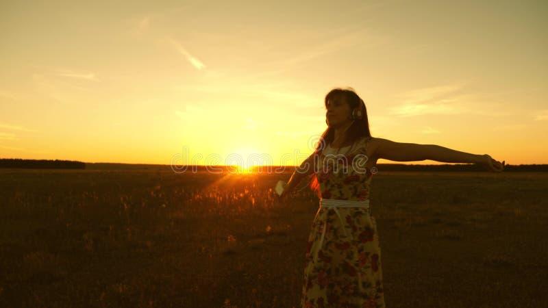 Gelukkig meisje die aan muziek luisteren en in de stralen van een mooie zonsondergang in het park dansen Mooi meisje in hoofdtele royalty-vrije stock afbeeldingen