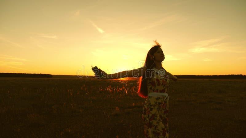 Gelukkig meisje die aan muziek luisteren en in de stralen van een mooie zonsondergang in het park dansen Mooi meisje in hoofdtele royalty-vrije stock afbeelding