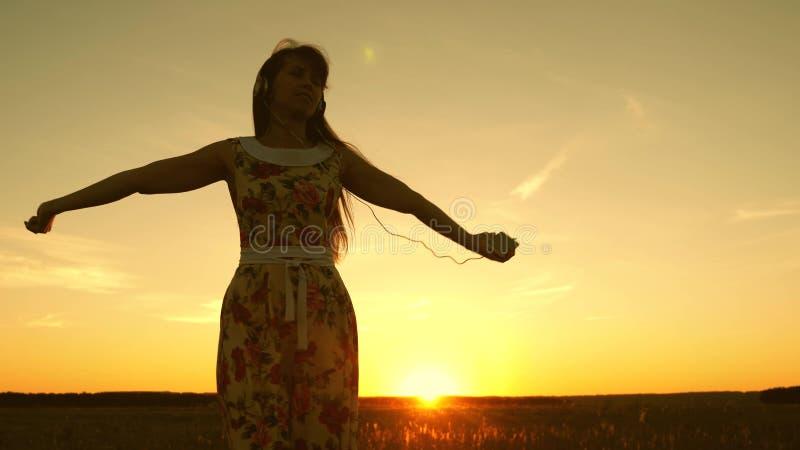 Gelukkig meisje die aan muziek luisteren en in stralen van een mooie zonsondergang tegen de hemel dansen jong meisje in hoofdtele royalty-vrije stock foto's